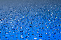 Gotas del agua en una superficie brillante fotos de archivo