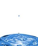 Gotas descendentes del agua en superficie del agua Foto de archivo