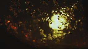 Gotas do fluxo da chuva abaixo do vidro contra o fundo do bokeh de carros moventes vídeos de arquivo