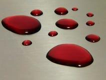 Gotas do vinho vermelho em um metal Foto de Stock