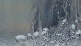 Gotas do volume de água para baixo belamente no vidro filme