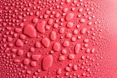 Gotas em um cor-de-rosa, fundo da água do resíduo metálico iluminado com uma luz delicada foto de stock royalty free