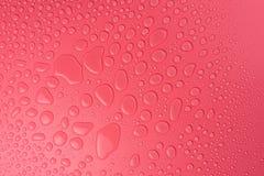 Gotas em um cor-de-rosa, fundo da água do resíduo metálico iluminado com uma luz delicada fotografia de stock