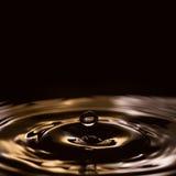 Gotas líquidas espirrar ouro, preto, ondas do branco Fotografia de Stock