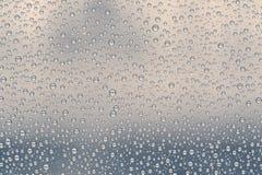 Gotas múltiplas da água ou pingos de chuva de tamanhos diferentes em um vidro de janela Foto de Stock Royalty Free