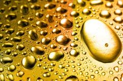 Gotas minúsculas del agua del oro fotografía de archivo