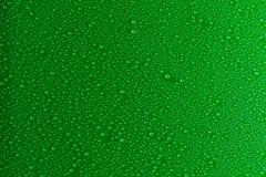 Gotas pequenas da água em um verde, fundo do resíduo metálico iluminado com uma luz delicada fotos de stock royalty free