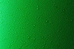 Gotas pequenas da água em um verde, fundo do resíduo metálico iluminado com uma luz delicada imagem de stock
