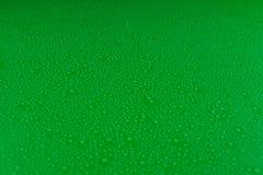 Gotas pequenas da água em um verde, fundo do resíduo metálico iluminado com uma luz delicada foto de stock