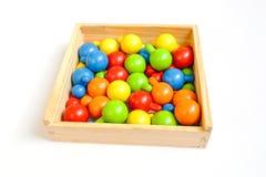 Gotas redondas multicoloras de madera en una caja de madera en un fondo blanco fotos de archivo libres de regalías