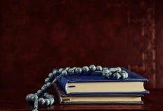Gotas y libros de oración del rosario en la tabla Fotos de archivo