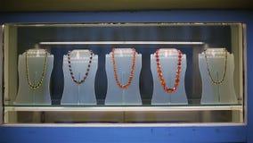 Gotas y pulseras ambarinas en una demostración-ventana de la tienda de la joyería almacen de metraje de vídeo