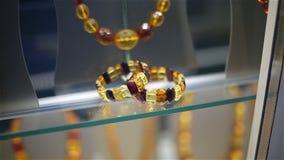 Gotas y pulseras ambarinas en una demostración-ventana de la tienda de la joyería almacen de video