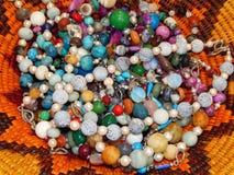 Gotas y pulseras de piedras semipreciosas en una placa de mimbre Fotografía de archivo libre de regalías
