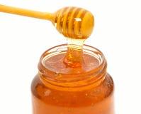 Goteador de la miel y tarro de la miel aislado Imagen de archivo
