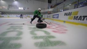 Goteando, muchacho del niño del jugador de hockey en patines con el duende malicioso de los movimientos del palillo alrededor del metrajes