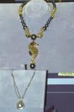 gotee el collar, adornado con piedras preciosas y un colgante bajo la forma de casa JUNWEX Moscú de la joyería del esteta del sea Imagen de archivo libre de regalías
