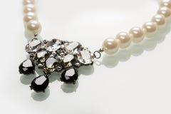 Gotee el collar con las piedras negras en un blanco Imagen de archivo libre de regalías
