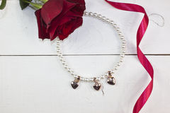 Gotee el collar con los corazones de oro en la madera blanca Fotos de archivo libres de regalías