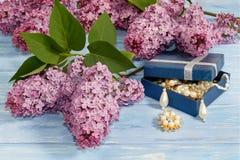 Gotee la joyería en caja azul y ramas de la lila en la tabla de madera fotografía de archivo