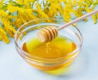 Gotejamento do mel de um dipper de madeira do mel na bacia de vidro em um fundo azul Fotos de Stock Royalty Free