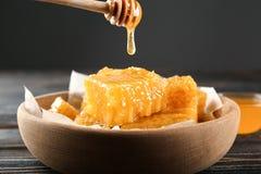 Gotejamento do mel do dipper nos favos de mel Fotos de Stock