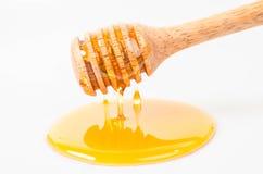 Goteo de la miel con el palillo de la miel Fotos de archivo libres de regalías