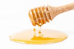 Goteo de la miel con el palillo de la miel Foto de archivo libre de regalías