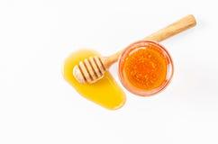 Goteo de la miel con el palillo de la miel y la miel en vidrio Imagen de archivo libre de regalías