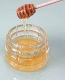 Goteo de la miel con los palillos especiales en un tarro para la miel Imagen de archivo