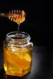 Goteo de la miel de la cuchara en el tarro de cristal con el peine Imagen de archivo libre de regalías