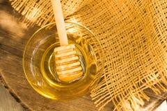 Goteo de la miel de un cazo de madera de la miel en fondo borroso Imagenes de archivo