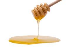 Goteo de la miel de una cuchara de madera. Imagen de archivo