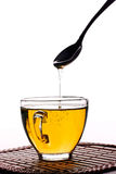 Goteo de la miel de una cuchara en la taza de té aislada Imagen de archivo