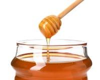 Goteo de la miel del cazo en el tarro en el fondo blanco Imagen de archivo