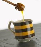 Goteo de la miel en el crisol Fotos de archivo libres de regalías