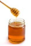 Goteo de la miel en el tarro sobre blanco Fotos de archivo libres de regalías
