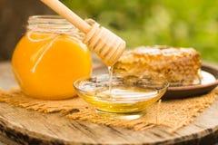 Goteo de la miel en tarro en la tabla Foto de archivo