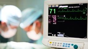 Goteo intravenoso con los cirujanos en fondo metrajes