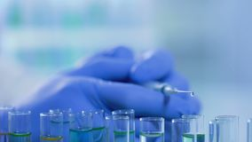 Goteo líquido de la jeringuilla en los tubos de ensayo, desarrollo de la droga en laboratorio almacen de video