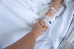 Goteo paciente de la mano que recibe una solución salina y una oxigenación en la cama en hospital fotos de archivo libres de regalías