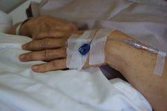 Goteo paciente de la mano que recibe una solución salina y una oxigenación en la cama en hospital imagen de archivo