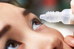 Goteos adolescentes de la muchacha en la medicación paciente del ojo imagen de archivo