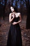 一个美丽的哀伤的goth女孩在树丛里站立 免版税库存图片