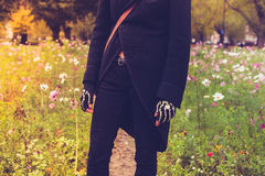Goth dressed in black standing in meadow Royalty Free Stock Photos