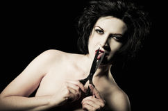 Goth girl cutting her tongue off with scissors. Closeup Royalty Free Stock Images