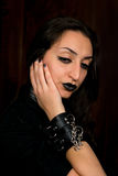 Goth girl with dark hair and dark eyes looking down with her hand on her face Royalty Free Stock Photography