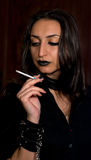 Goth girl with dark hair and dark eyes smoking a cigarette Stock Images
