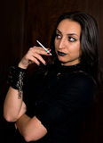 Goth girl with dark hair and dark eyes smoking a cigarette Royalty Free Stock Photos