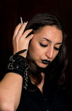 Goth girl with dark hair and dark eyes smoking a cigarette and adjusting her hair Stock Images